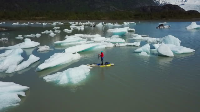 Aerial View Man on SUP Between Small Icebergs