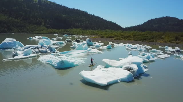 Aerial View Man Paddling Between Small Icebergs