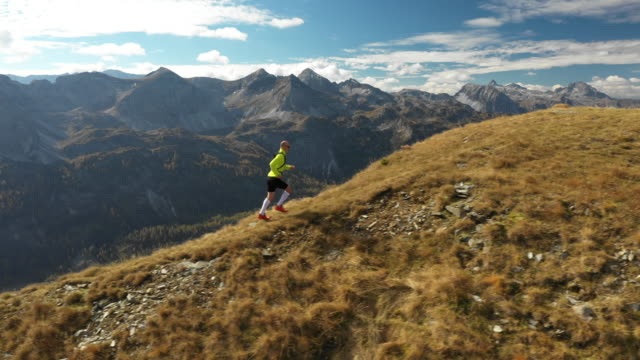 4K aerial view man trail running on ridge in mountains