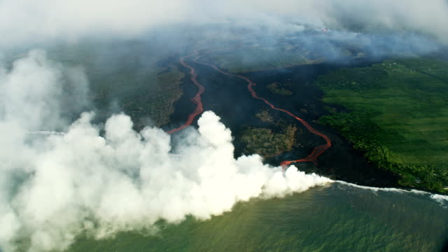 aerial view molten lava pouring into pacific ocean - natural condition stock videos & royalty-free footage