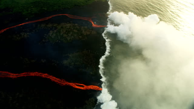 aerial view molten lava pouring into pacific ocean - earthquake stock videos & royalty-free footage
