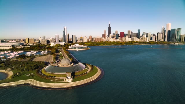 aerial view moving in over shedd aquarium toward chicago skyline - shedd aquarium stock videos and b-roll footage