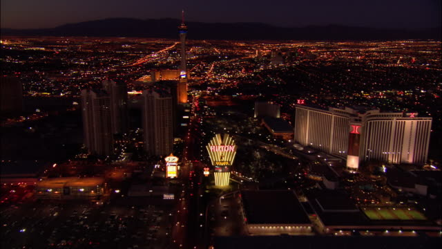 aerial view moving south over hotels along the las vegas strip towards the stratosphere tower / night / las vegas, nevada - ラスベガスヒルトン点の映像素材/bロール