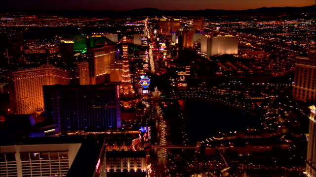 Aerial view moving South over traffic on Las Vegas Boulevard South and hotels along the Las Vegas Strip / replica Eiffel Tower at Paris Las Vegas / night / Las Vegas, Nevada