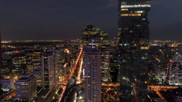 aerial view moving up through silom city downtown in bangkok at night - bangkok stock-videos und b-roll-filmmaterial