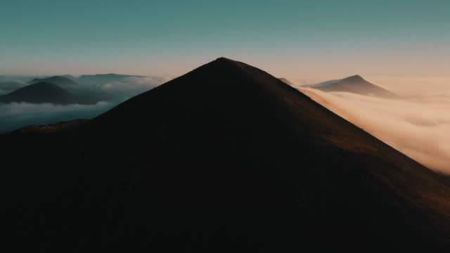 vídeos de stock e filmes b-roll de aerial view moving up to reveal a volcanic scene during sunrise, lanzarote, spain - beauty in nature