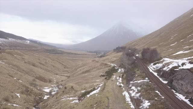 aerial view near glencoe in winter, argyll and bute, scottish highlands, scotland, united kingdom, europe - rail transportation stock videos & royalty-free footage