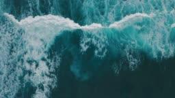 Aerial view ocean waves break into foam along the shore