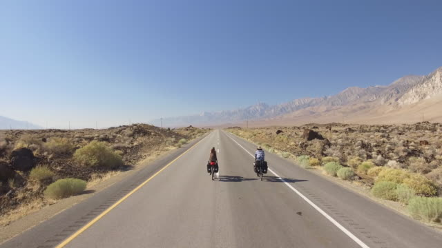 Aerial view of 2 bicyclists following empty road across desert
