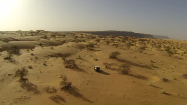 aerial (drone) view of 4x4 truck driving through remote desert terrain - mauritania stock videos & royalty-free footage