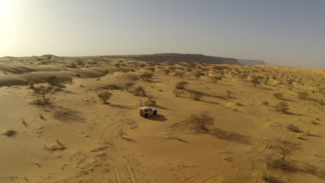 aerial (drone) view of 4x4 truck driving through remote desert terrain - durability stock videos & royalty-free footage
