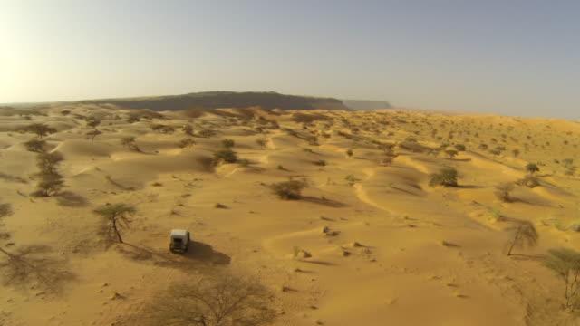 リモート砂漠の地形を介して駆動 4 × 4 トラックの空中 (ドローン) ビュー - モーリタニア点の映像素材/bロール