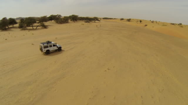 aerial (drone) view of 4x4 truck driving through remote terrain - mauritania stock videos & royalty-free footage