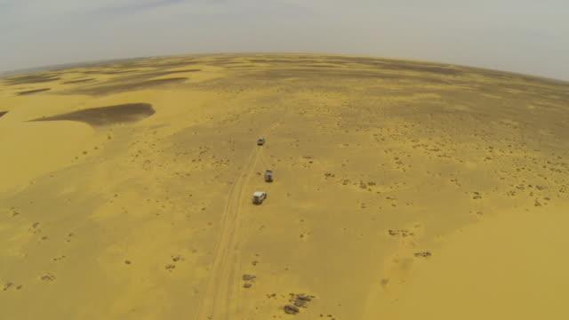 Aerial (drone) view of 4x4 trucks driving through remote terrain