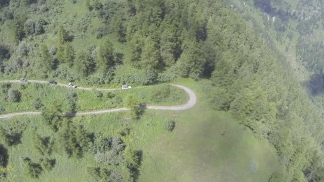 vista aerea (drone) di camion 4x4 che guidano attraverso terreni remoti - durevolezza video stock e b–roll