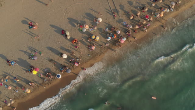 aerial view of a beach with crowd enjoying sea - parasol stock videos & royalty-free footage