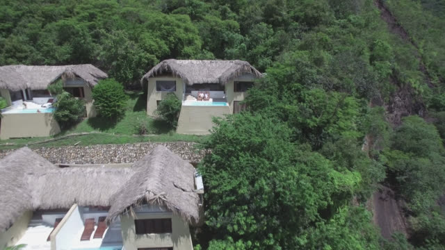 aerial view of a beautiful couple at their hotel hut enjoying the sun - separation stock videos and b-roll footage