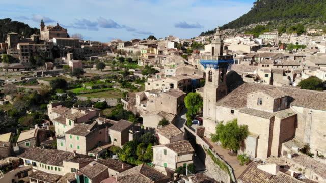 vídeos de stock e filmes b-roll de aerial view of a beautiful mediterranean town of valldemosa in mallorca island. - imagem tonalizada