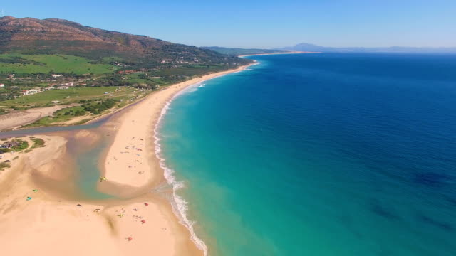 aerial view of a big dune sand with ocean and africa coast behind it - andalusien stock-videos und b-roll-filmmaterial
