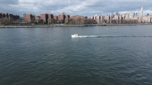 aerial view of a boat on new york city's east river - river east stock videos & royalty-free footage