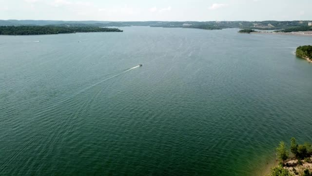 vídeos de stock e filmes b-roll de aerial view of a boat sailing in the distance on the lake in branson missouri - missouri