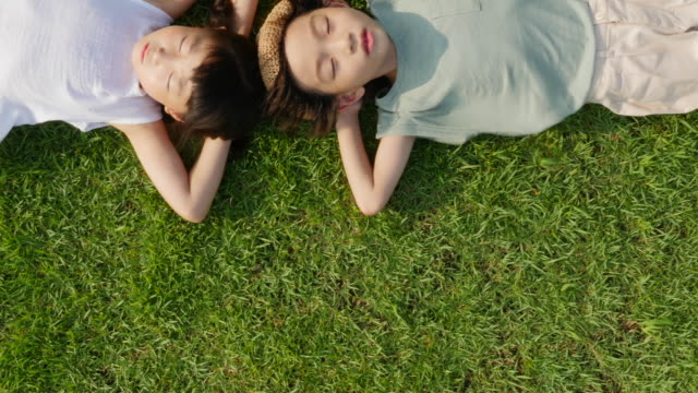 Aerial view of a boy and a girl lying on lawn in summer at Seoulforest (the third largest park in Seoul city)