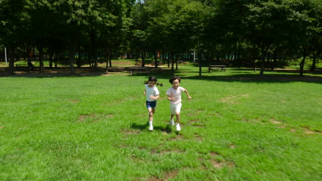 Aerial view of a boy and a girl running in summer at Seoulforest (the third largest park in Seoul city)