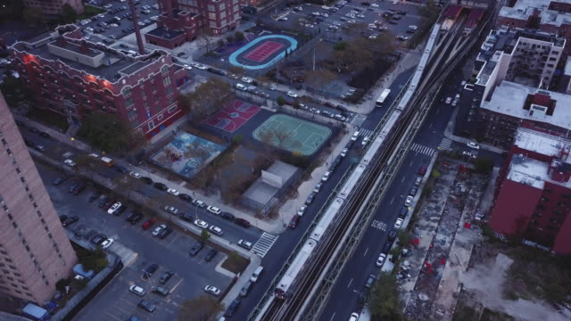 Aerial view of a Brooklyn bound subway train at dusk.