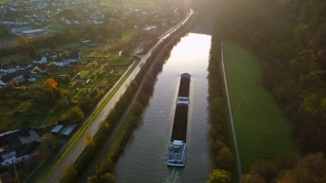 vídeos de stock, filmes e b-roll de aerial view of a cargo vessel on saar river near staadt, saar valley, rhineland-palatinate, germany - renânia palatinado