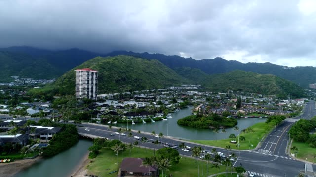 aerial view of a cloudy honolulu hawaii with a freeway and residences along water outlets - honolulu stock videos and b-roll footage