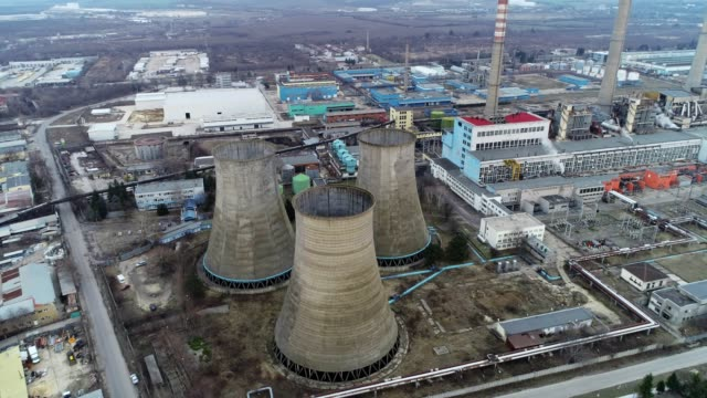 Aerial view of a coal-fired power station near a marine harbour at sunset, industrial construction cranes, coal mining industry, environmental conservation and issues, Germany and sustainability in power and fuel generation,