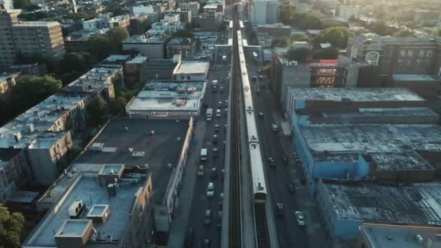 aerial view of a commuter train exiting brooklyn at sunset - aerial stock videos & royalty-free footage