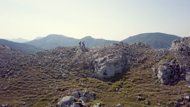 Aerial view of a couple hiking on the top of a mountain