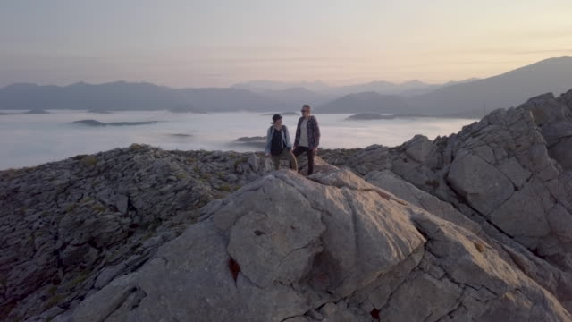 vidéos et rushes de aerial view of a couple on the top of a rocky mountain - sommet montagne