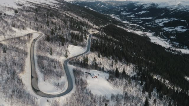 aerial view of a curvy road on a snowy mountain side in telemark, norway. - telemark stock videos and b-roll footage