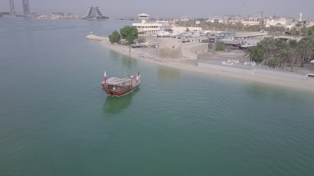 aerial view of a dhow approaching the shoreline in front of bu maher fort. - ダウ船点の映像素材/bロール