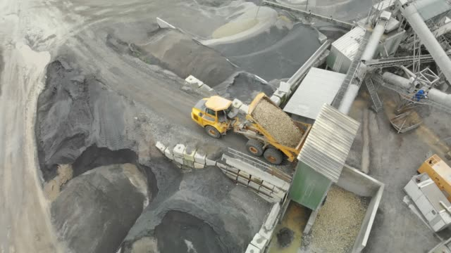 aerial view of a dumper truck unloading gravel into a pit - quarry stock videos & royalty-free footage