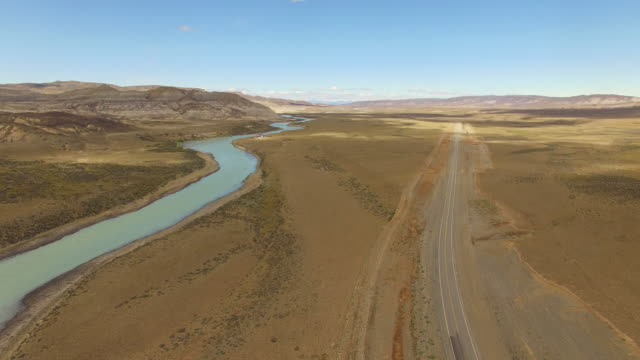 vídeos de stock, filmes e b-roll de aerial view of a empty road next a river at patagonia, argentina - 20 segundos ou mais