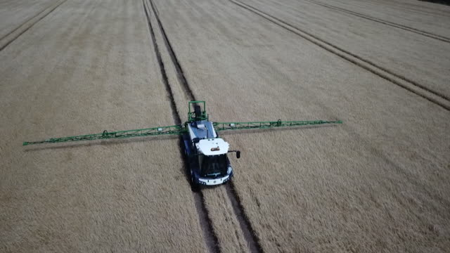 aerial view of a farm vehicle fertilising crops - crop stock videos & royalty-free footage