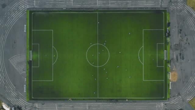 vídeos y material grabado en eventos de stock de vista aérea de un equipo de fútbol que juega en clima frío. campo de fútbol en la vista superior - partido rondas deportivas