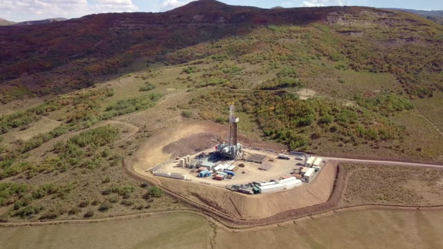 aerial view of a fracking drilling rig in the autumn mountains of colorado - drill stock videos & royalty-free footage
