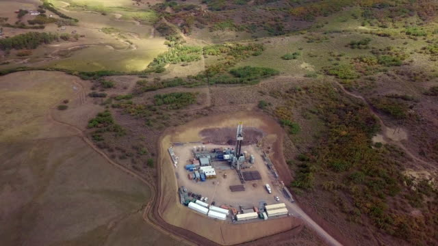 aerial view of a fracking drilling rig in the autumn mountains of colorado - fracking stock videos and b-roll footage