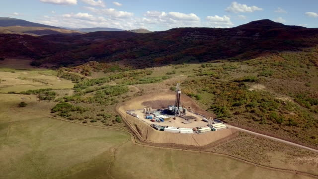 aerial view of a fracking drilling rig in the autumn mountains of colorado - drilling rig stock videos and b-roll footage
