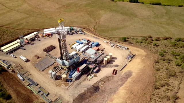 aerial view of a fracking drilling rig in the autumn mountains of colorado - industria petrolifera video stock e b–roll