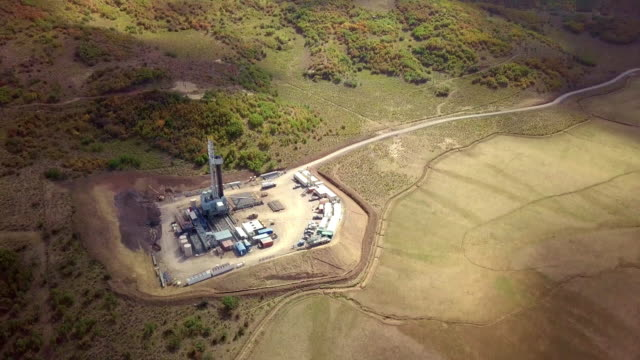 aerial view of a fracking drilling rig in the autumn mountains of colorado - land stock videos & royalty-free footage