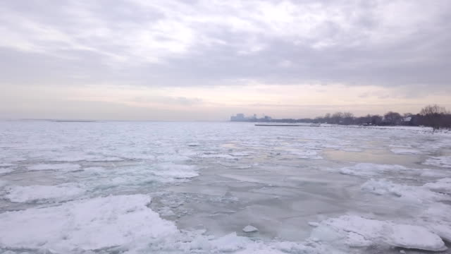 aerial view of a frozen lake michigan towards chicago illinois - lago michigan video stock e b–roll