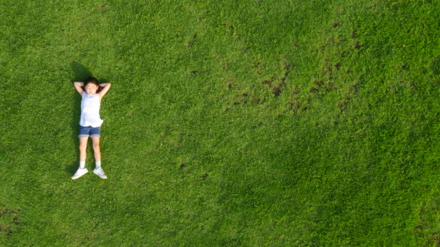 vidéos et rushes de aerial view of a girl lying on lawn in summer at seoulforest (the third largest park in seoul city) - être étendu