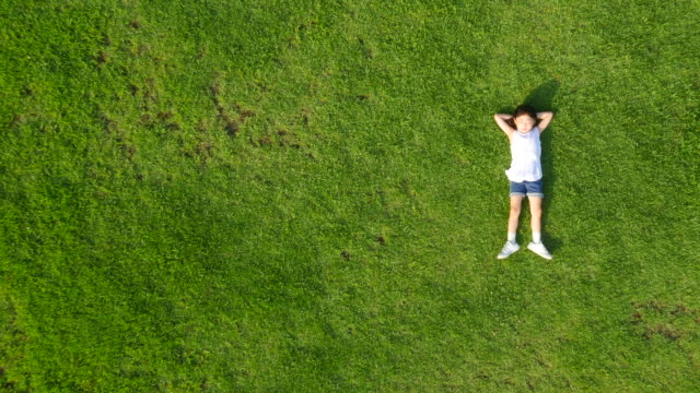 Aerial view of a girl lying on lawn in summer at Seoulforest (the third largest park in Seoul city)