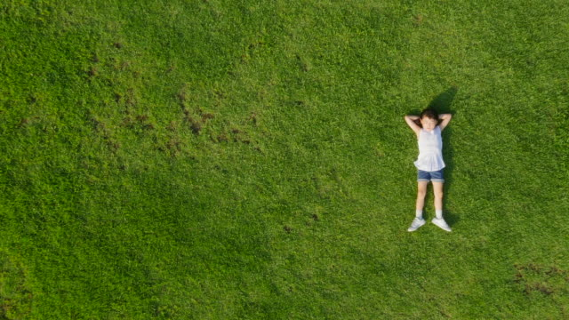 vídeos y material grabado en eventos de stock de aerial view of a girl lying on lawn in summer at seoulforest (the third largest park in seoul city) - manos detrás de la cabeza