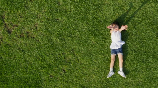Aerial view of a girl lying on lawn shaking her hands toward the sky in summer at Seoulforest (the third largest park in Seoul city)